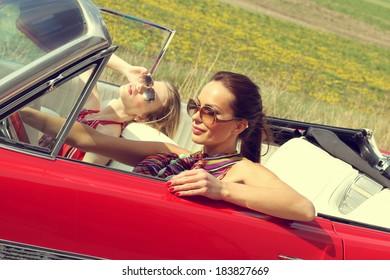 Beautiful women driving a red car wearing accesoriess