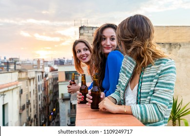 Beautiful women enjoying a beer on a rooftop in Barcelona. Three girls drinking a beer and having fun during a party at sunset on a rooftop with Gothic quarter on background in Barcelona
