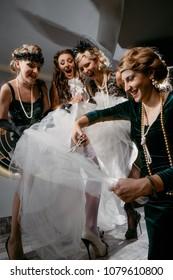 Beautiful women in evening dresses with scissors cutting bride`s dress