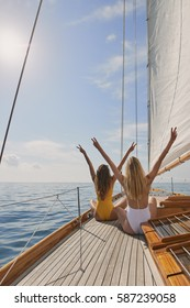 Beautiful women friends celebrate arms raised peace sign on sailboat in ocean on luxury lifestyle happy adventure travel vacation