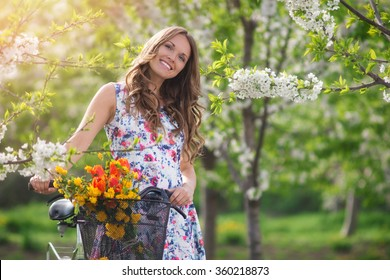Beautiful women In the Fruit Garden at spring with bicycle