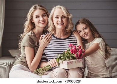 Beautiful women generation: granny with presents, mom and daughter are hugging, looking at camera and smiling while sitting on couch at home