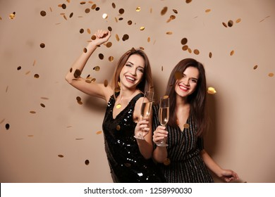 Beautiful women with glasses of champagne and confetti on color background