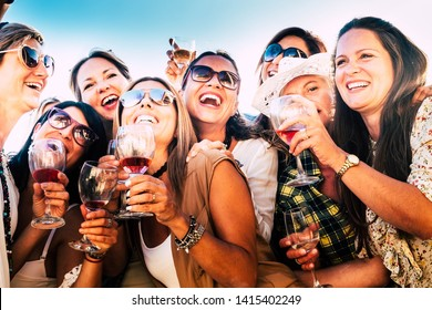 Beautiful women in group celebrate the friendship  with some wine glass. Nine caucasian people enjoying the sunset with aperitif