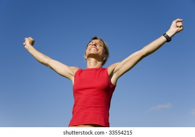 Beautiful women with her arms outstretched on a blue sky