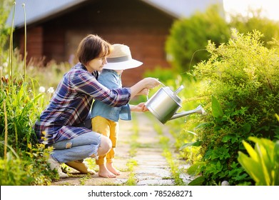 Beautiful women and her cute grandson watering plants in the garden at summer sunny day. Gardening activity with little kid and family
