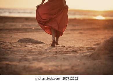 beautiful women in long orange dress is running on the beach at sunset
