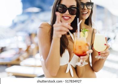 Beautiful women on sunny beach enjoying cocktails