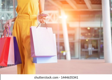 Beautiful women with shopping bags and credit card enjoying in shopping standing outdoors of shopping mall, shopping concept