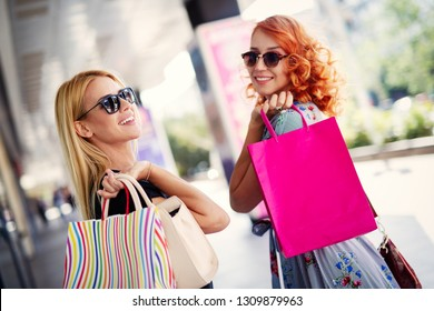 Beautiful women with shopping bags walking at the mall
