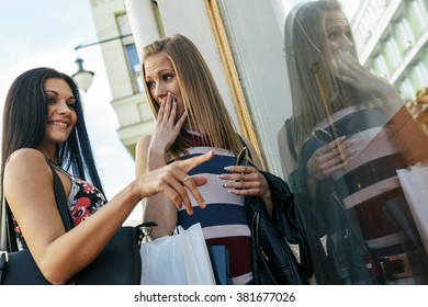 Beautiful women shopping outdoors and holding bags