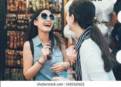 Beautiful women smiling trying on new sunglasses shopping with best friend. Two lovely young ladies enjoying shopping for eyewear together. Friendship having fun relax playful lifestyle concept