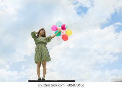 Beautiful women standing on the lake  alone and holding a balloon Time of happiness And rest