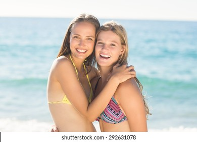 Beautiful women standing together arm around at the beach