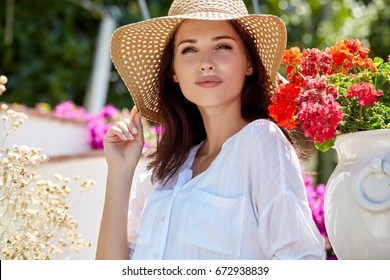 Beautiful women in a straw hat at the summer garden.