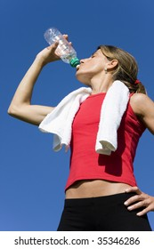 Beautiful women with towel drinking water after fitness