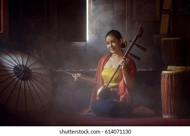 Beautiful women in traditional dress costume playing treble fiddle. Treble fiddle or soprano sounded string Thai music instrument, Thai Cultural Arts Conservation Concept.