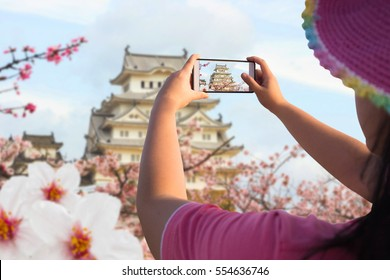 A beautiful women traveler use mobile phone take a photo landscape Himeji castles One of Japan's premier historic castles, Japan