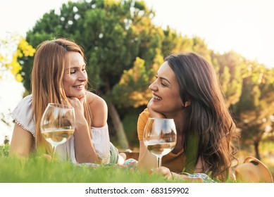 Beautiful women using mobile in the park. Friends and summer concept.