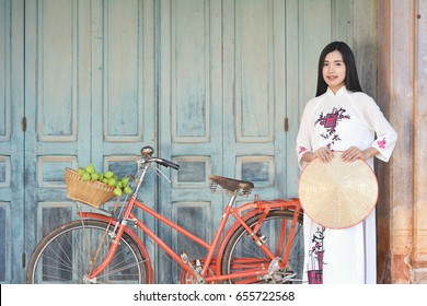 Beautiful women Vietnam with white Ao Dai dress and red bicycle in old city , selective and soft focus of face color vintage style