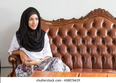 Beautiful women wearing the Islamic headscarf sitting on a couch big brown. In front of a white wall, smiled and waited.