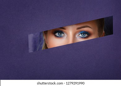 beautiful women's eyes look in the paper hole, bright make-up .