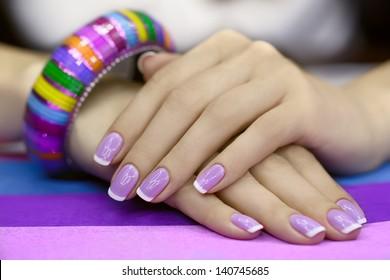 Beautiful women's manicure with purple polish on the nails