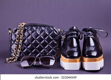 beautiful women's minimal set of fashion accessories on a black background. Ideal for blogs or magazines. Sunglasses, purse, shoes.