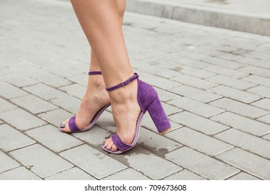 Beautiful women's tanned legs in violet suede heels sandals with dark pedicure. The girl walks around the city and stands on the pavement