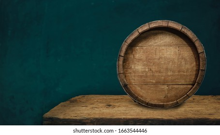 Beautiful wooden barrel and oak worn table of wood on a green wall pattern background for design.
