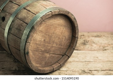 Beautiful wooden barrel on a old oak table and red wall background.