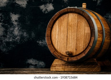 A beautiful wooden barrel and a worn oak wood table set against a dark wall pattern for the design.