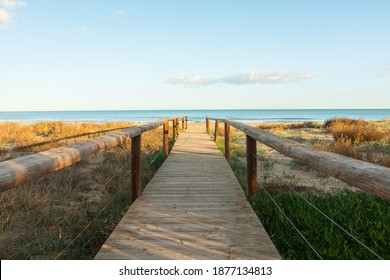 Beautiful wooden boardwalk leading to the beach. Perfect landscape photography with a dreamlike seascape horizon. POV postcard shot.