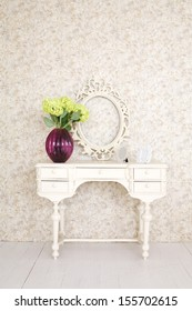 Beautiful wooden carved dressing table with blank frame in light room.