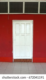 Beautiful wooden door painted white color with red wall and glass windows