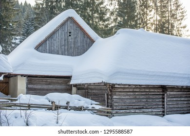 beautiful wooden house on the roof of which a thick layer of snow in a winter sunny day