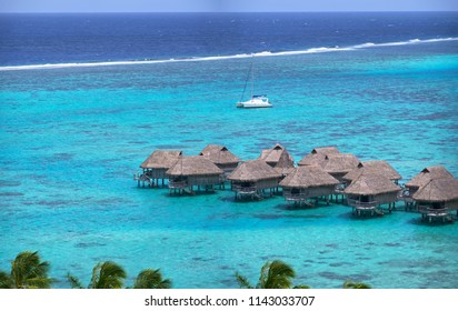 Beautiful wooden overwater villas overlook the endless calm turquoise colored ocean on a perfect summer day in the Seychelles. Spectacular view of breathtaking oceanfront apartments in the Maldives.
