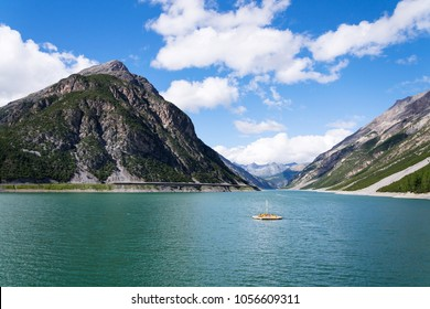 Beautiful wooden pier with benches and deckchairs floating on Lago di Livigno with Corno Brusadella Mountain in background, Livigno, Italy, sunny summer day