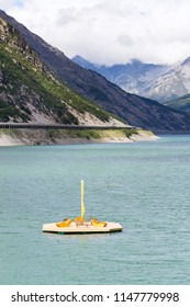 Beautiful wooden pier with benches and deckchairs floating on Lago di Livigno, Livigno, Italy, sunny summer day