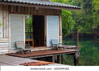 Beautiful wooden terrace or balcony with two chair near beach above the water, Thailand