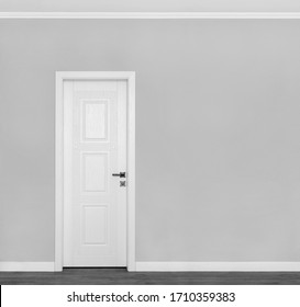 Beautiful wooden white door on empty grey wall with copy space for your text. Interior concept