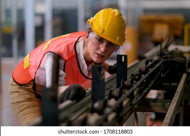 Beautiful worker or technician woman look forward through rail of some machine in factory work.