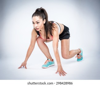 Beautiful workout woman in race start position. Studio shot.