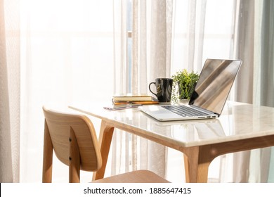Beautiful workspace - online remote work from home concept. A wooden table with computer laptop, smartphone, coffee cup beside the window balcony with sun light shine through the curtain. No people.