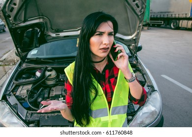 Beautiful and worried brunette beside the broken car calling for help with mobile phone.