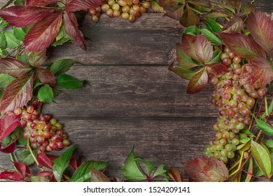 Beautiful wreath frame with grapes, leaves and vine on wooden boards. Flat lay style. Fall concept.