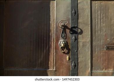 beautiful wrought iron door knob on an old weathered brown entrance door
