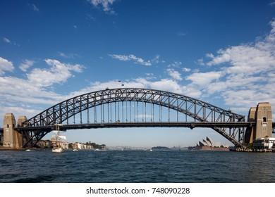 A beautiful yacht sail's nearby Harbor bridge in Sydney, summer 2017