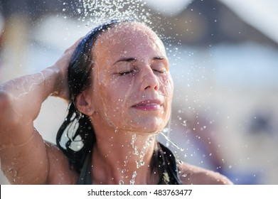 Beautiful yang woman posing under beach shower.