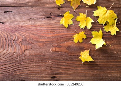 Beautiful yellow autumn leaves on wooden background as corner frame